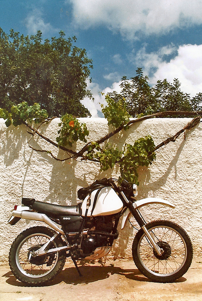 A white motorcycle with high fenders and knobby tires in front of a white wall.