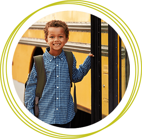 Elementary School Boy Getting Onto A Yellow School Bus