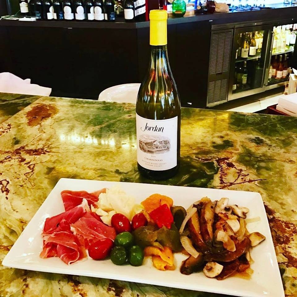 Antipasto on a table with a bottle
