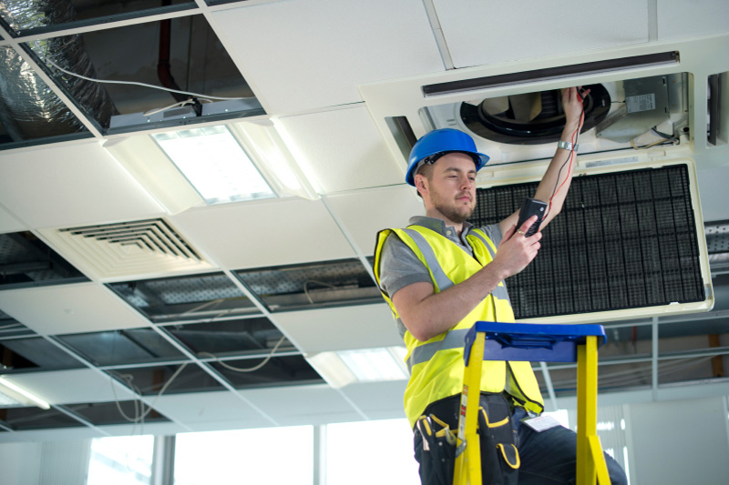 Electrician fitting air conditioning