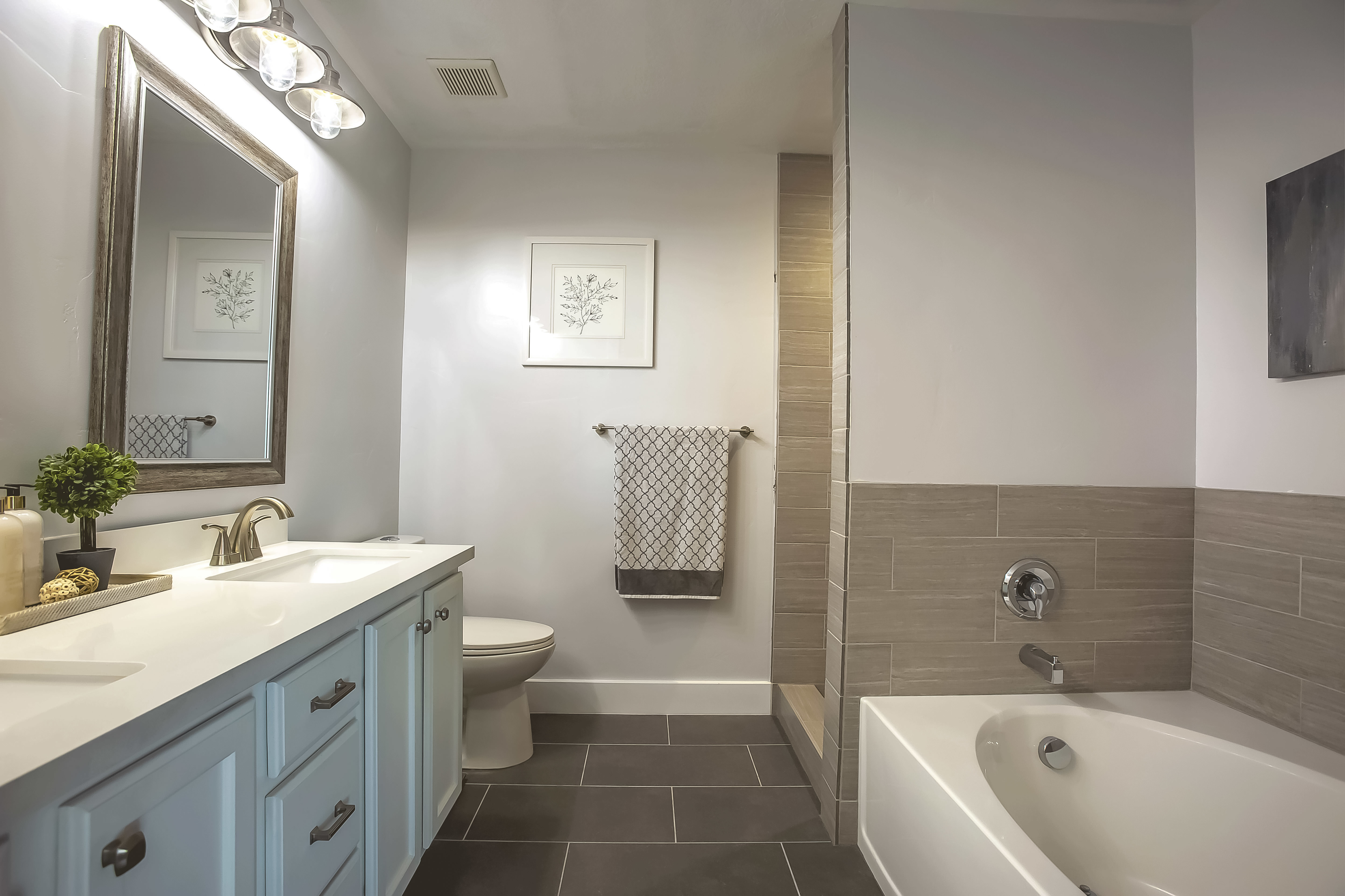 Medium size bathroom remodel with vintage/industrial vanity sconces .  Double vanity with white quartz countertop and drop mount sink with brushed nickel hardware.  Slate like tile job  for both tub and shower.