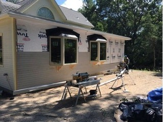 Install bay windows and red cedar clapboard siding.
