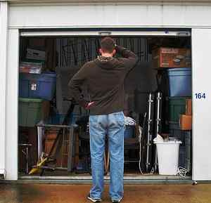 man standing in front of his storage unit scratching his head