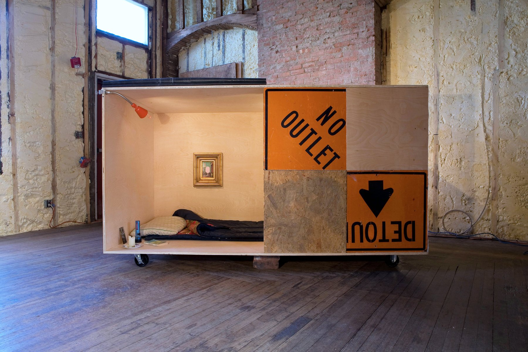 A box made from plywood and orange signs contains a bed and a painting.