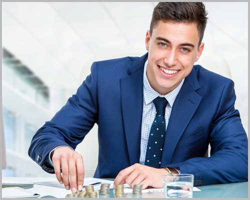 Businessman Counting Money at Desk