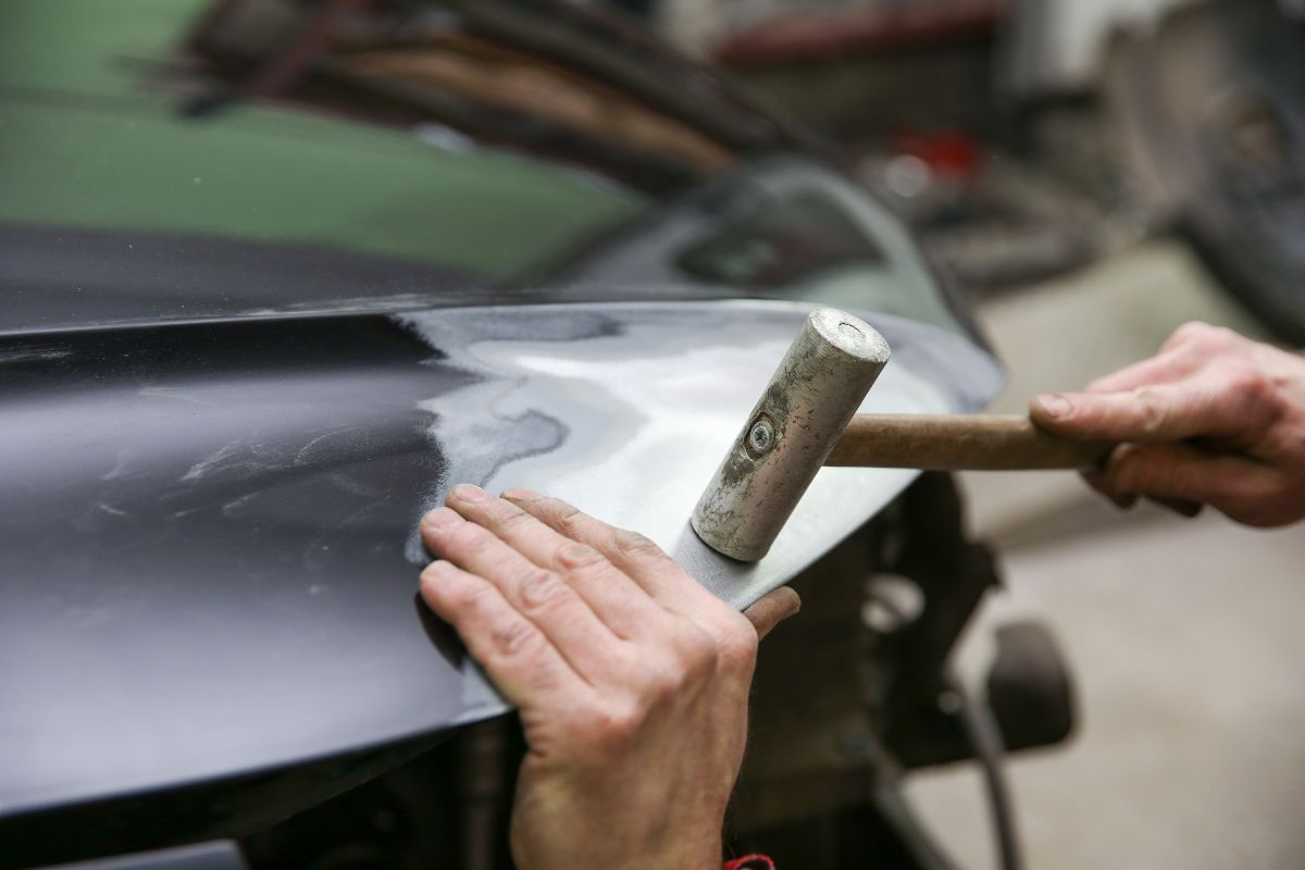Mechanic is aligning car body part by hammer