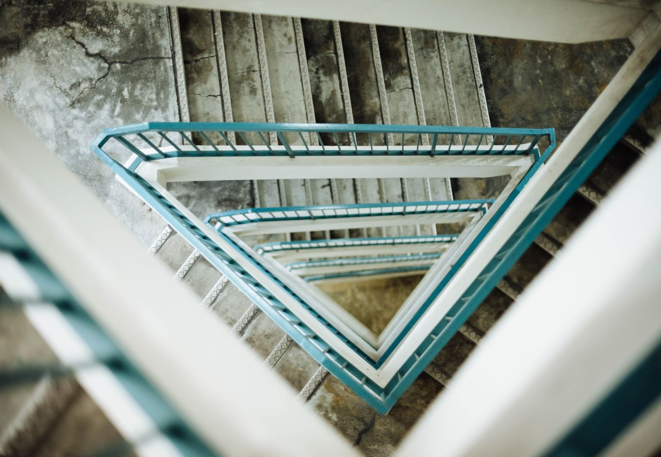 Long stair case with blue handrails