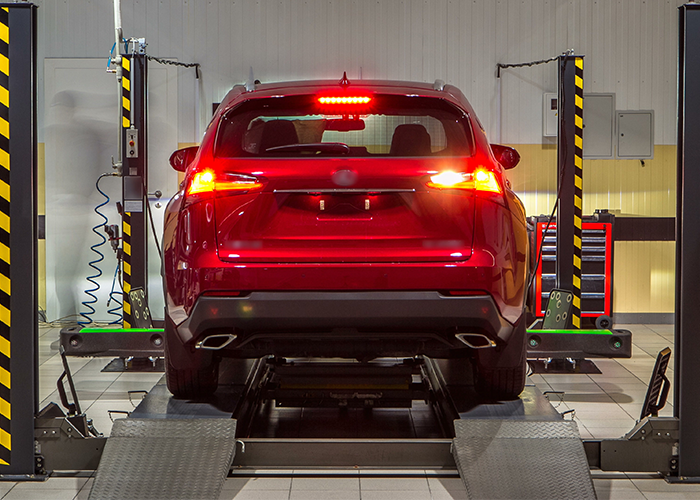Car on stand with sensors on wheels for wheels alignment camber check in workshop of Service station timelapse.