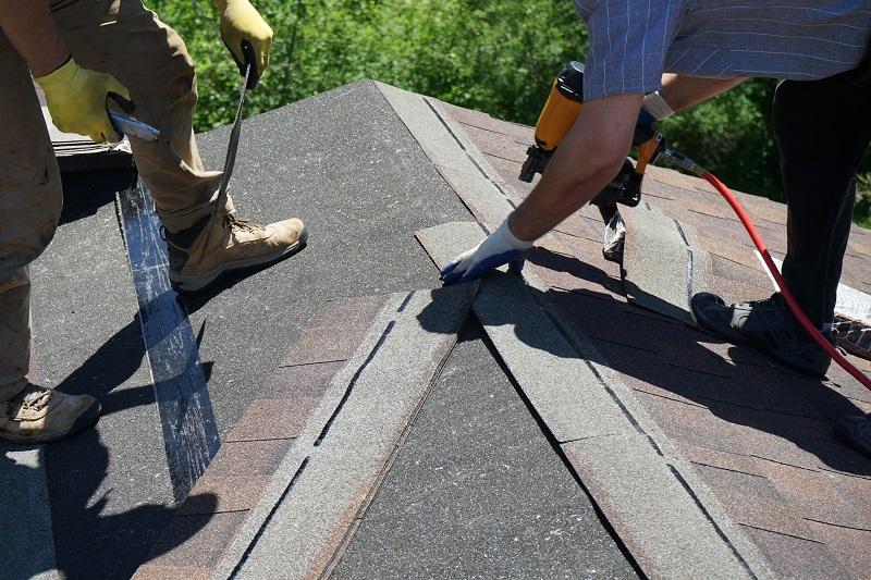 People on Roof Repairing Asphalt Shingles