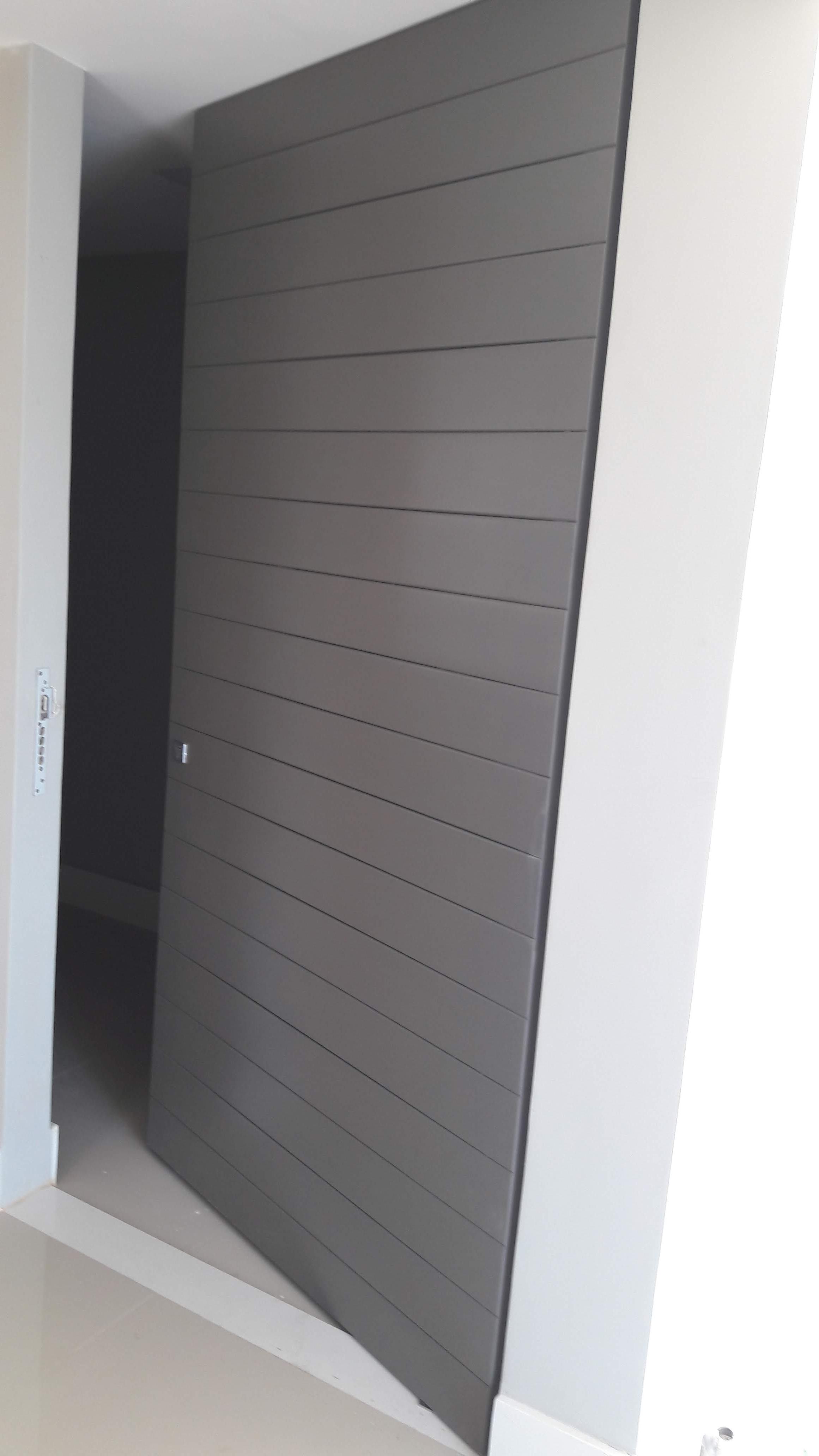 Porta 704 -Porta de entrada, frisada, sistema de abertura pivotante e pintada em laca cinza.