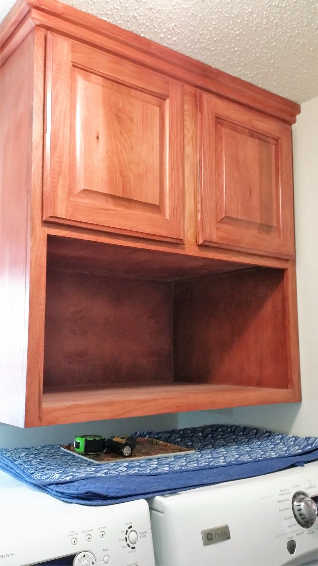 Hickory Utility cabinet features raised  panel doors with a Sedona red stain.