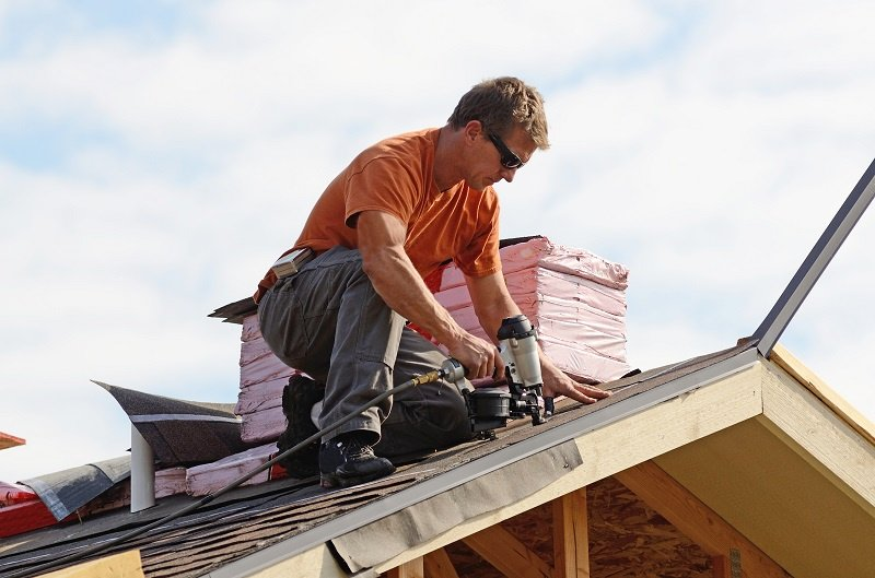 Roofer with Nail Gun on Roof