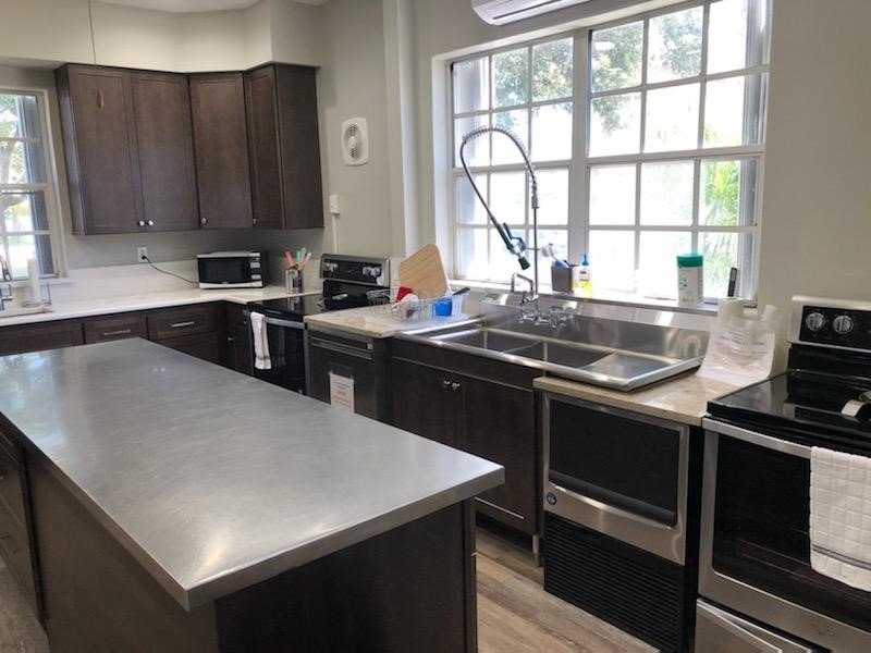 Large kitchen with matching Island featuring an oversize commercial grade sink and double ovens.