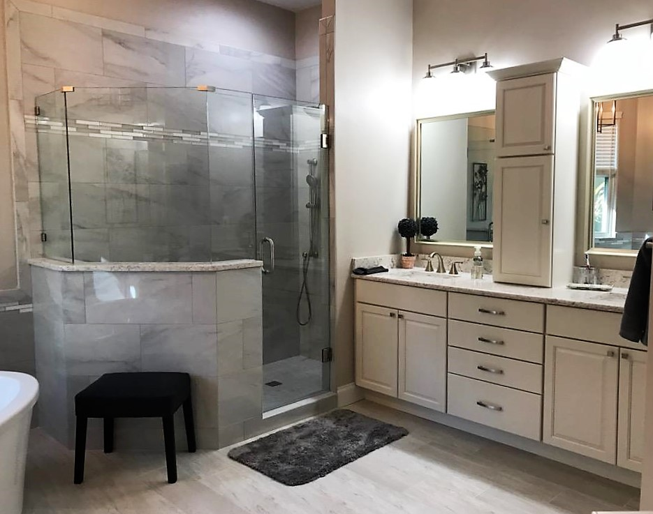 Double vanity featuring framed mirrors and lighting with additional cabinet  storage between the dual sinks.