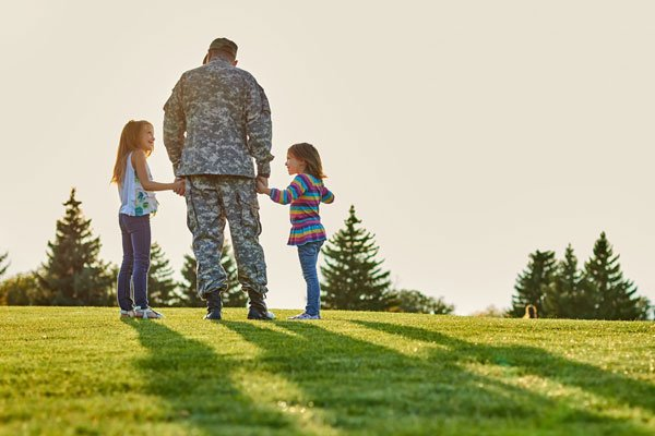 Man In Military Uniform Is Holding Hands Of Little Daughters