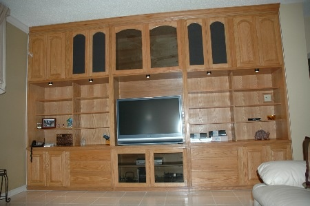 "13'x8'x20"" deep Media center is made of  red oak with a fruitwood stain. It features  dark tint glass for the use of remote controls,  adjustable shelves , cloth covered door panels for speaker system, and high  intensity lights for display areas."