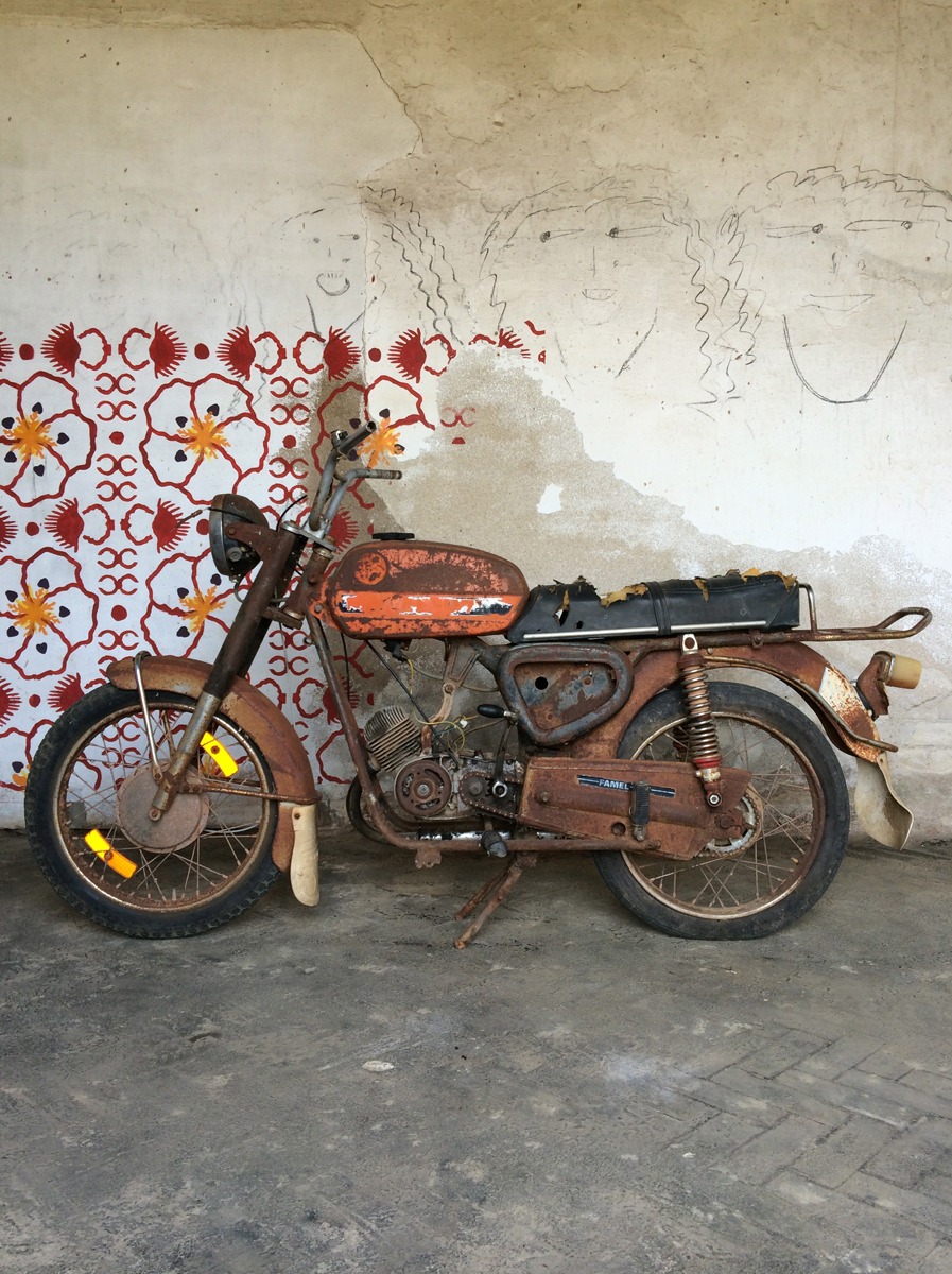 A rusty motorcycle against a wall with a floral mural and three hand-drawn faces.