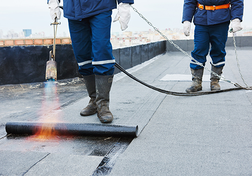 Flat Roof Installation. Heating and Melting Bitumen Roofing