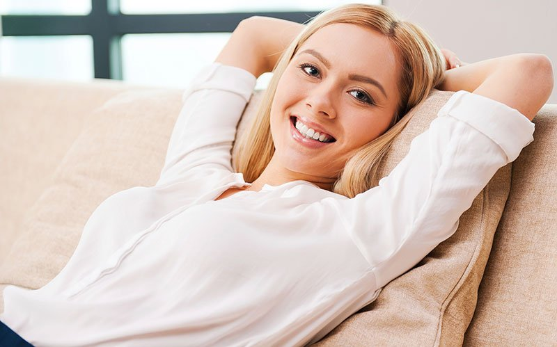Woman holding hands behind head while relaxing