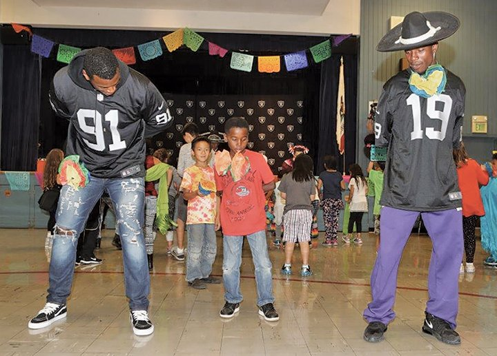 Raiders rookies Shilique Calhoun (91) and Jaydon Mickens (19) performed Ballet Folklorico dance routines on Monday with students from Roosevelt Elementary School.