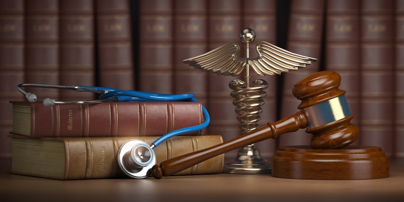 Gavel next to stethoscope and books