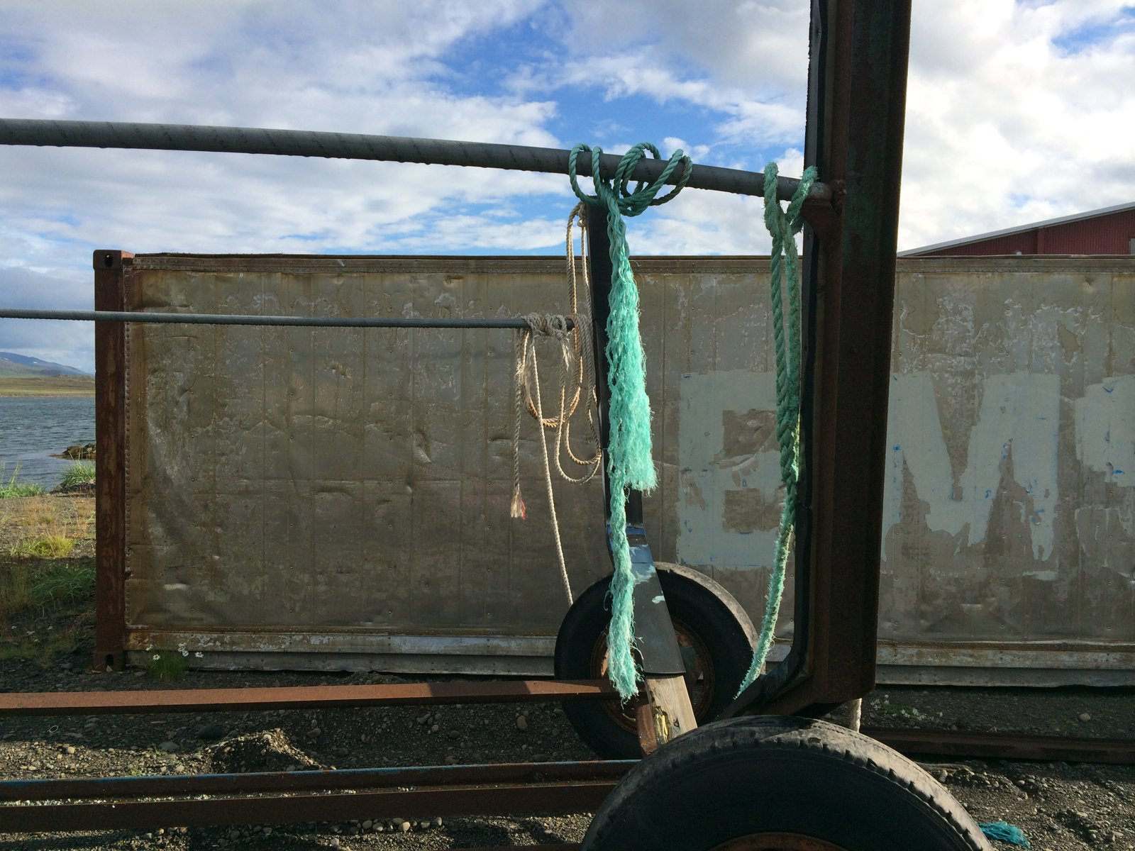 Frayed teal-colored and white rope hangs from an old rusty metal trailer frame.