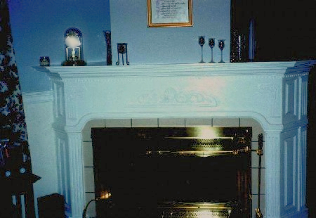 Wrap around fireplace features 22,5 degree  angle raised paneled sides with fluted pilasters.  The front features center carved appliques. A four  layer mantle with dentil molding finishes fireplace,