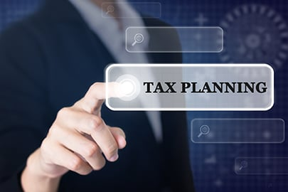 Businessman Pressing a TAX PLANNING Concept Button