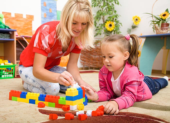 Teacher and child are playing with bricks