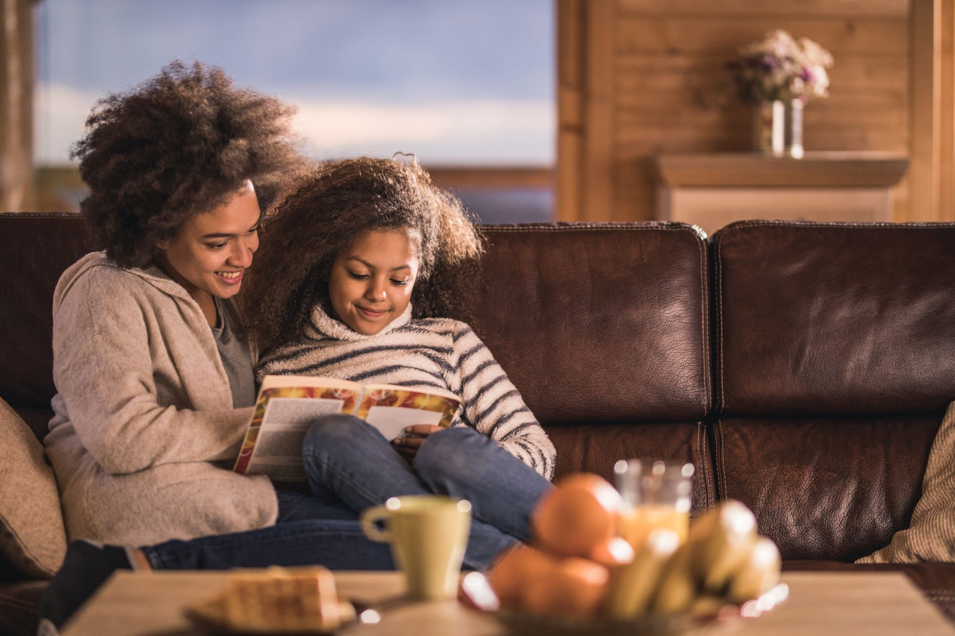 Relaxed African American mother and daughter reading a book on sofa