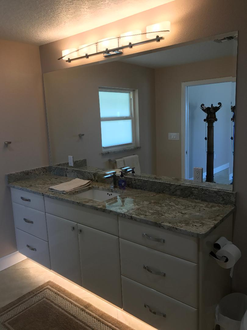 Featuring a sleek white vanity with under cabinet lighting.