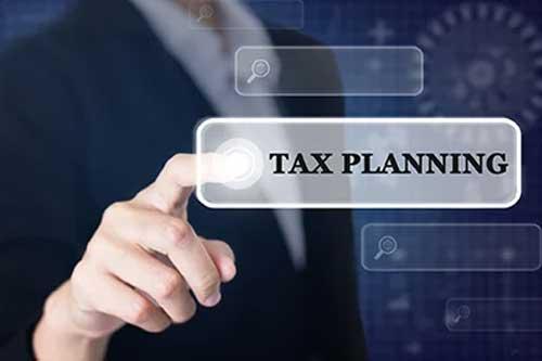 Businessman Pressing a TAX PLANNING Concept Button