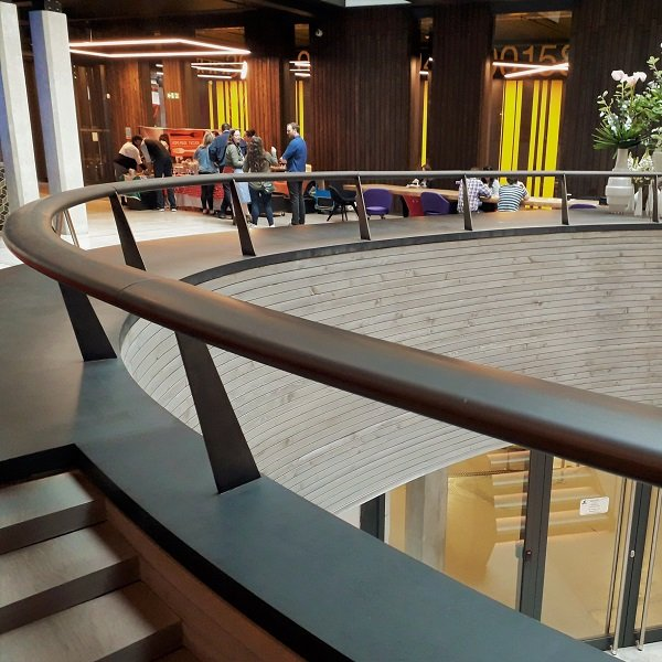 Metal coating at Alphabeta Building. Bronzed wooden handrail. Artistic Metals