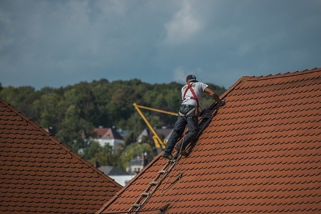 Roofer Standing On Red Roof