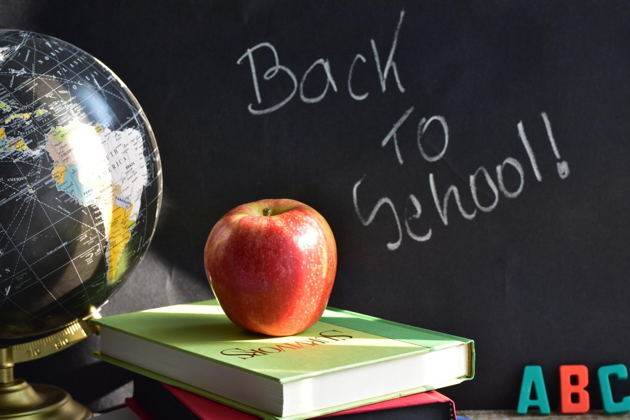 Blackboard, apple, books and globe in a classroom