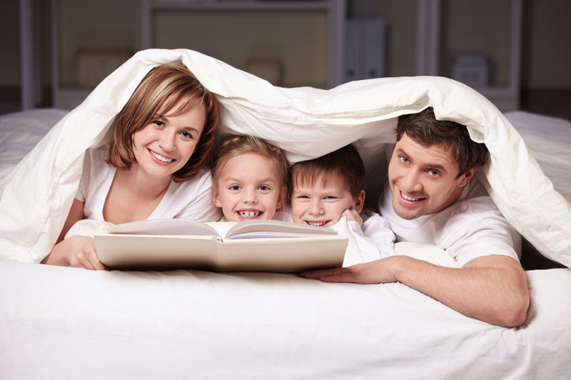 Happy family with a book on the bed