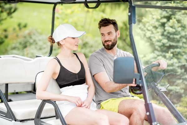 Young And Happy Couple Having Fun Driving A Golf Cart
