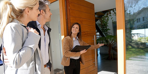 Real Estate Agent Inviting Couple to Enter House