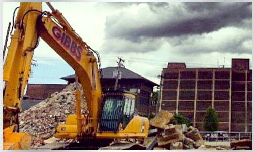 A Large Track Hoe Excavator Tearing Down an Old Hotel to.