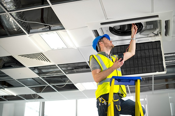 Man fitting commercial air conditioning