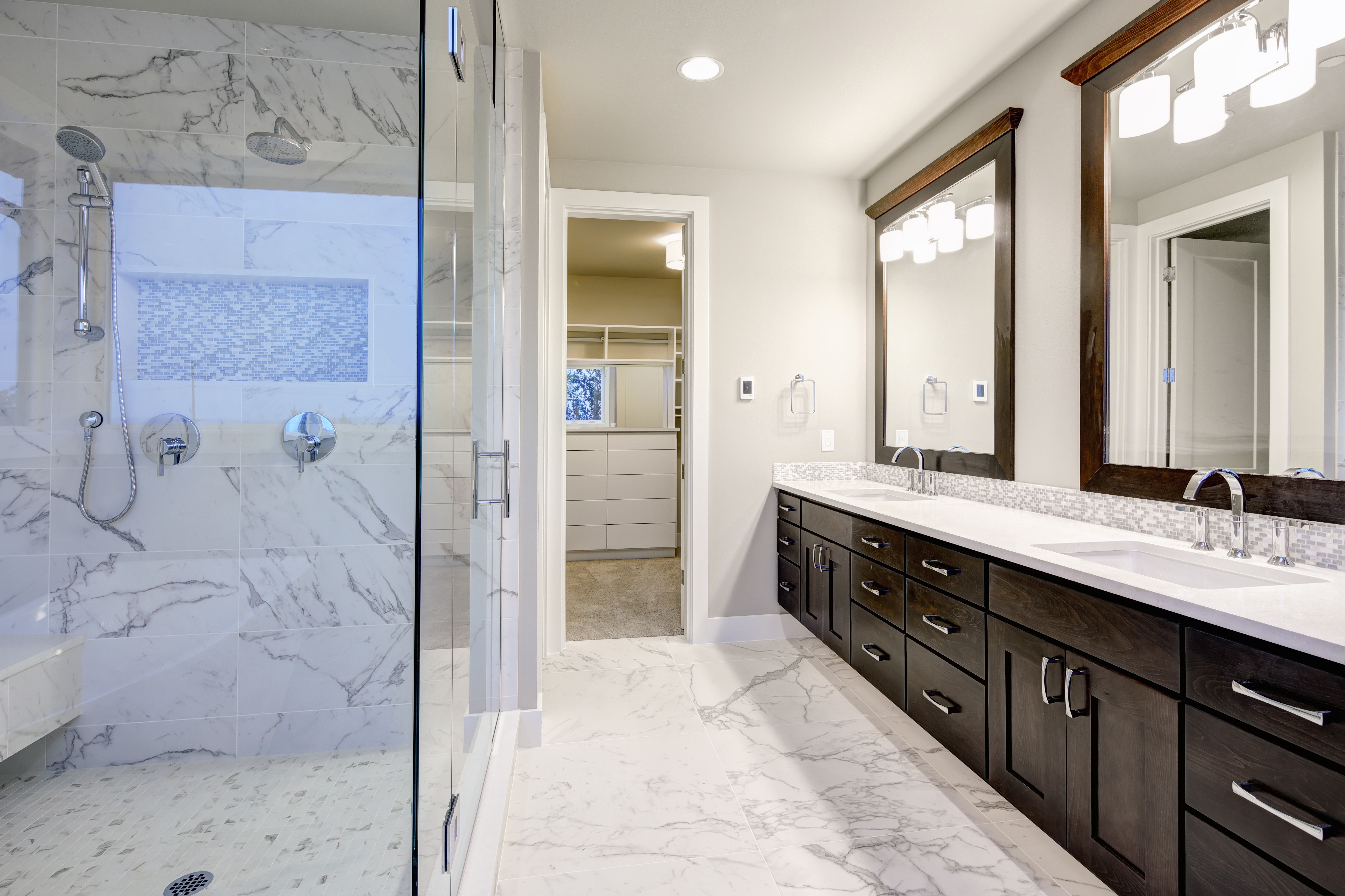 Medium size bathroom remodel featuring marble tile in the shower with niche and seating.  Beautiful espresso double vanity with white quartz countertops with drop sinks with a mosaic backsplash.