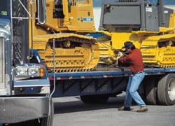 Man Securing Bulldozer to Flatbed Trailer