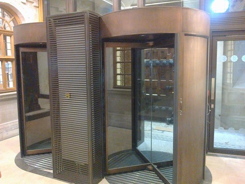 Bronze finish applied veneer coating on metal revolving doors. artisticmetals.co.uk