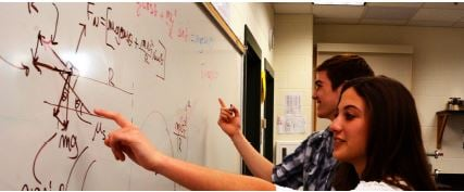 Two students analyzing a math problem in Physics.