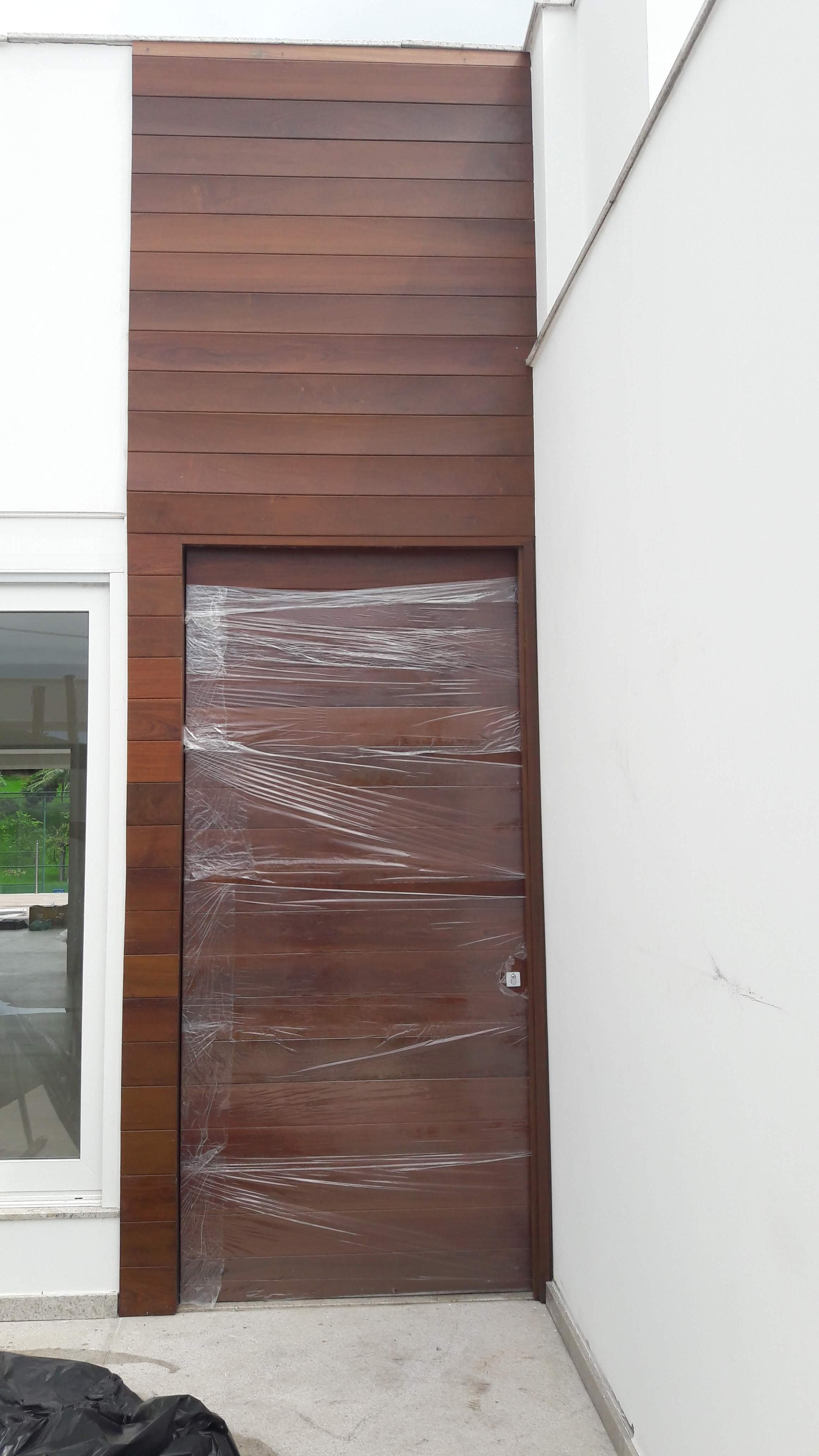 Porta 705 - Porta de madeira com  sistema de abertura pivotante, painel de madeira, envernizada.
