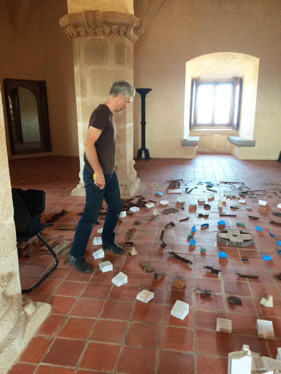 A man steps over rustic objects arranged in concentric circles on a red tile floor.