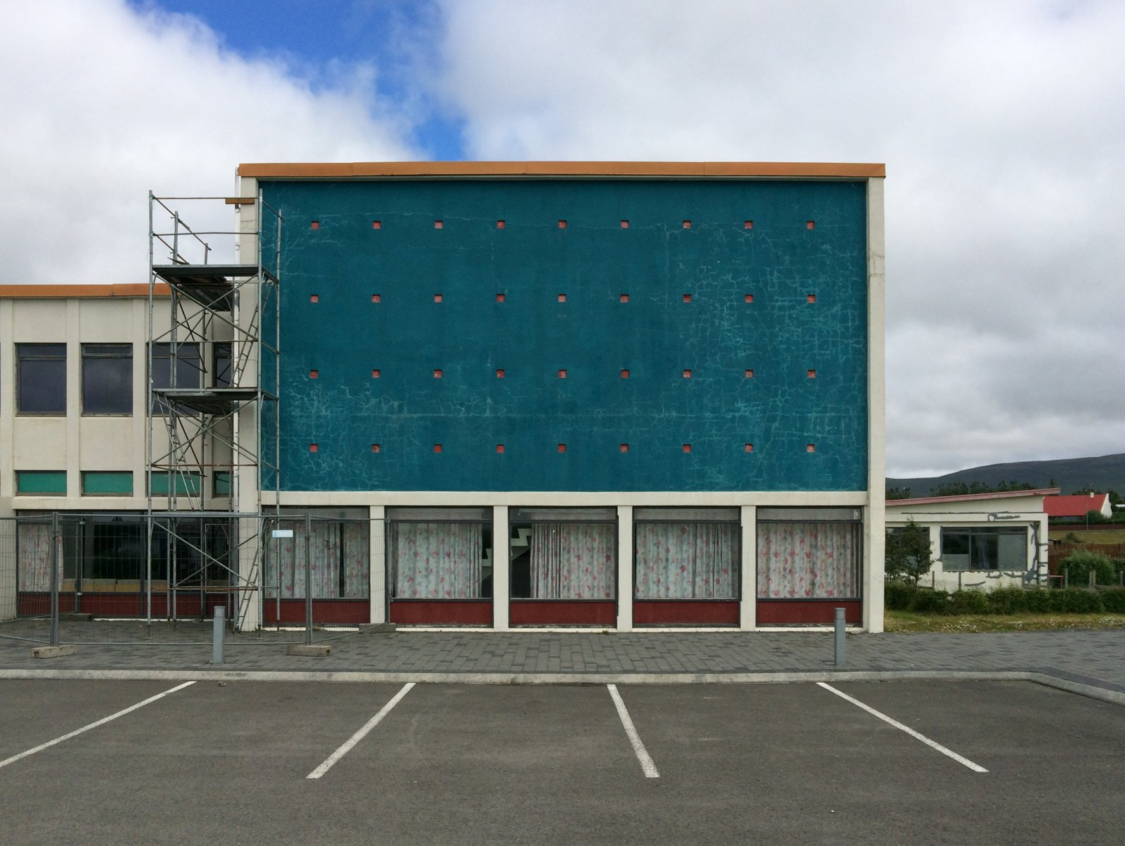 A commercial building with blank modernist turquoise facade and scaffolding.