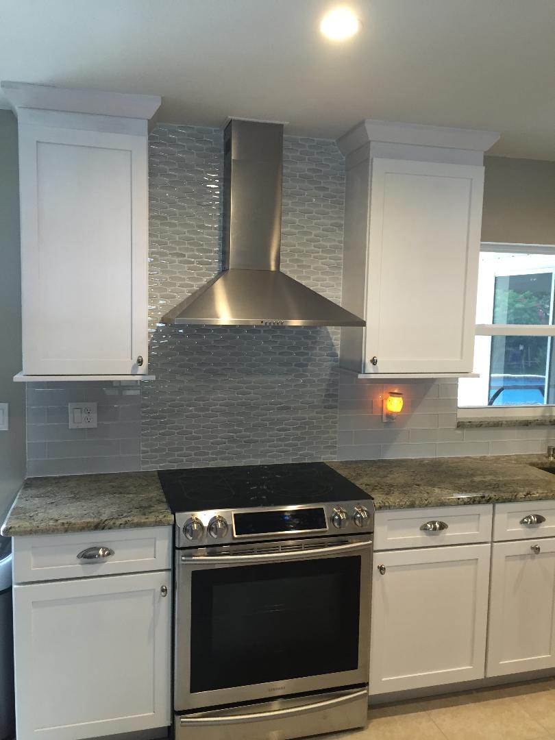 Gorgeous hood vent featuring a glossy patterned backsplash.