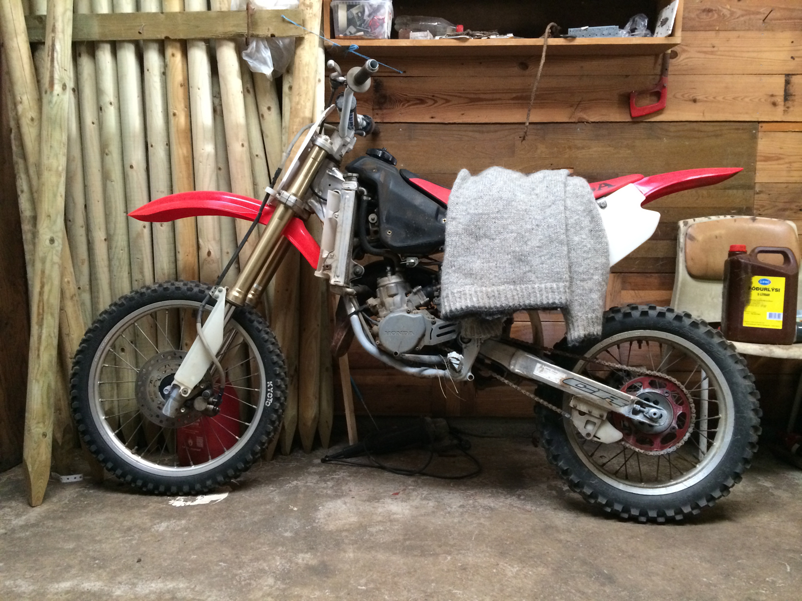 A motocross motorcycle, a sweater on the seat, leaning on a wall with staves.