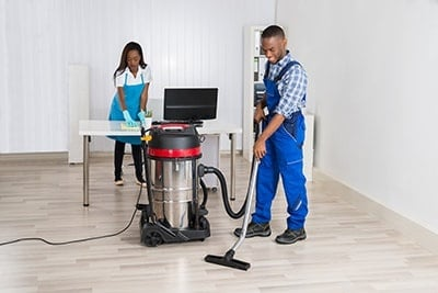 Male And Female Janitor Cleaning Office